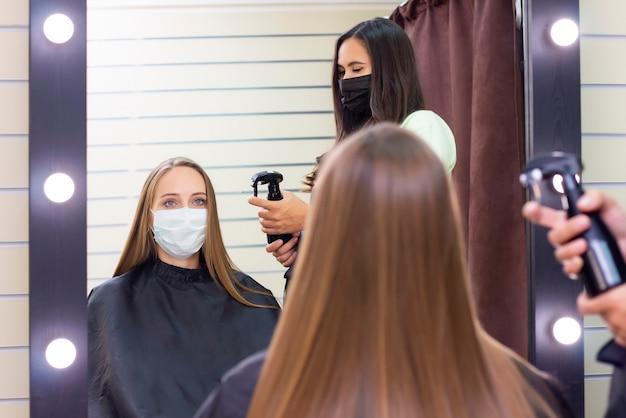 Jonge vrouw bij kapper die beschermend masker draagt wegens pandemie van het coronavirus