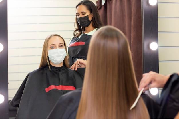 Jonge vrouw bij kapper die beschermend masker draagt