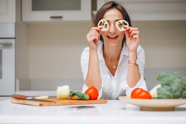 Jonge vrouw bij keuken kokend ontbijt