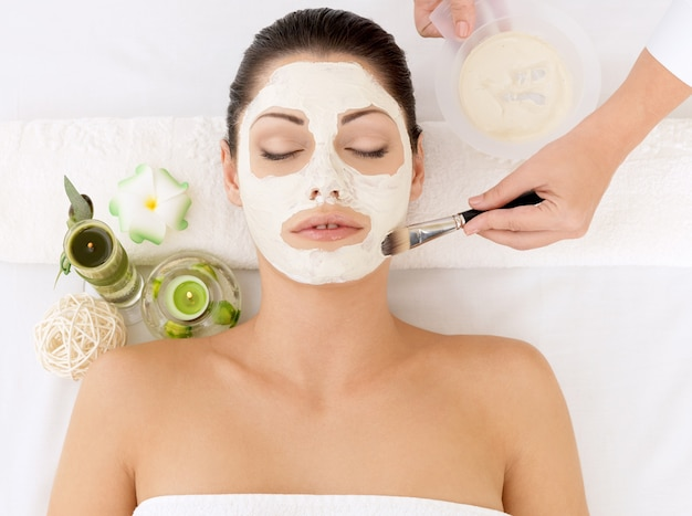 Jonge vrouw bij kuuroordsalon met kosmetisch masker op gezicht. hoge hoekfoto