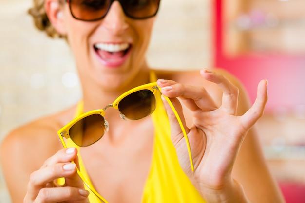 Jonge vrouw bij opticien met zonnebril
