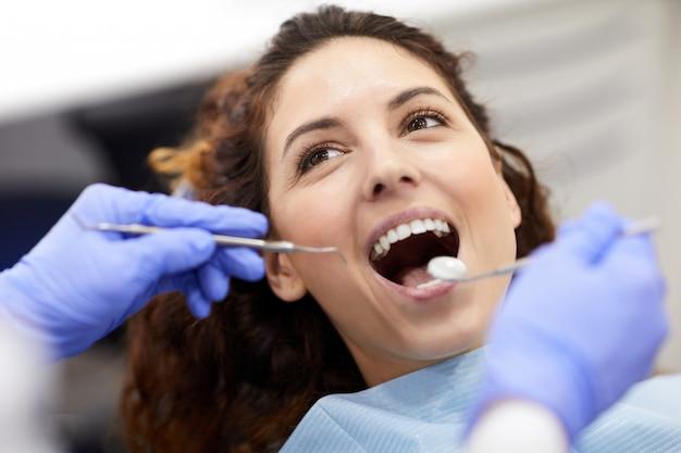 Jonge vrouw bij tandheelkundig examen
