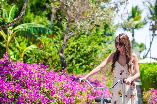 Jonge vrouw bij vakantie het biking bij bloeiende tuin