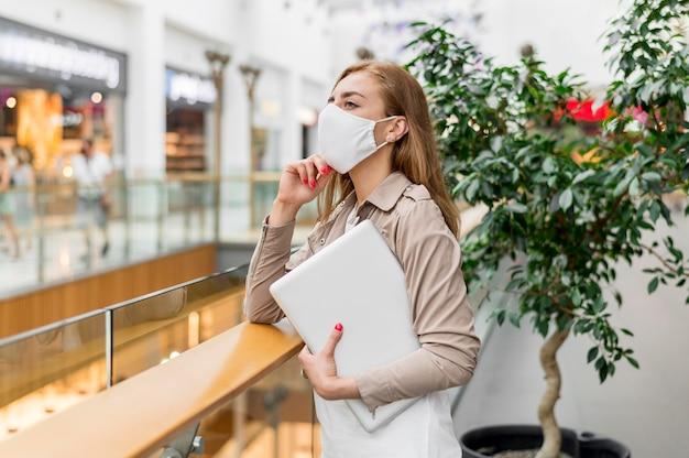 Jonge vrouw bij wandelgalerij met laptop die masker draagt