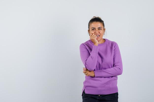 Jonge vrouw bijt vuist en kijkt peinzend