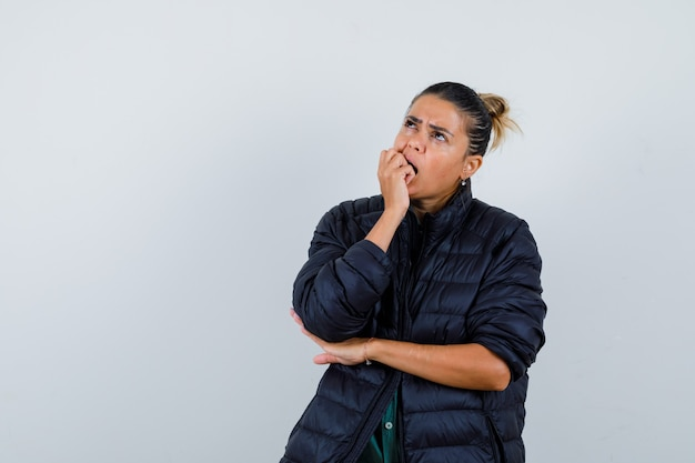 Jonge vrouw bijt vuist terwijl ze opkijkt in pufferjack en peinzend kijkt. vooraanzicht.