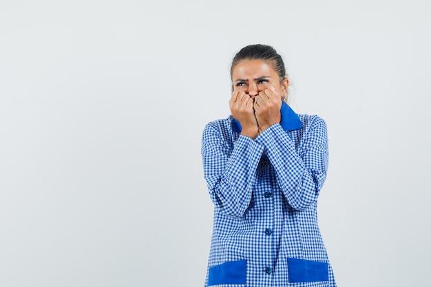 Jonge vrouw bijt vuisten in blauw pastel pyjama shirt en op zoek bang, vooraanzicht.