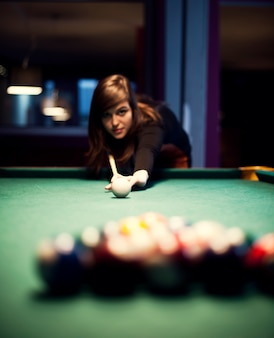 Jonge vrouw biljart spelen