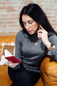 Jonge vrouw binnen sprekende slimme telefoon die agenda controleert
