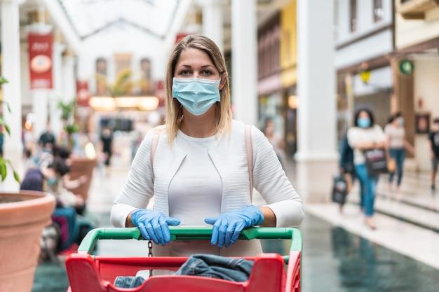 Jonge vrouw binnen winkelcomplex dat gezichts beschermend masker draagt