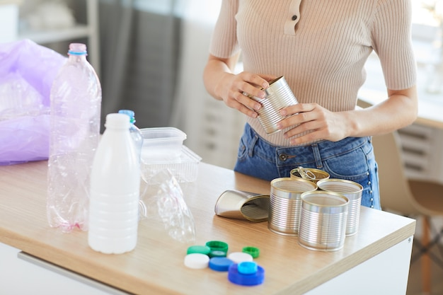 Jonge vrouw binnenshuis thuis scheiden van glas, blikjes en plastic afval