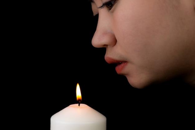 Jonge vrouw blaast een kaarsvlam op zwarte achtergrond
