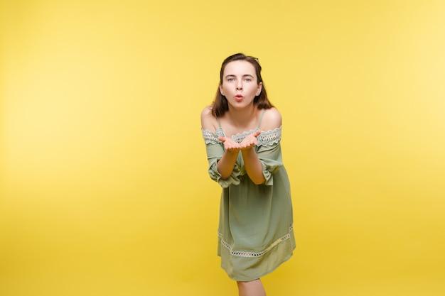 Jonge vrouw blaast luchtkus bij camera.