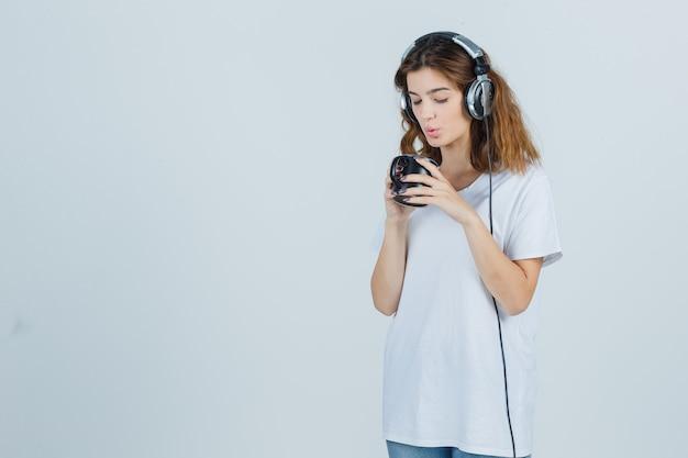 Jonge vrouw blaast op thee in beker in wit t-shirt en kijkt schattig, vooraanzicht.