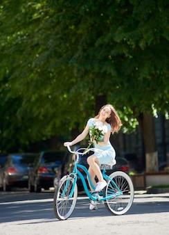 Jonge vrouw blauwe stadsfiets buiten rijden
