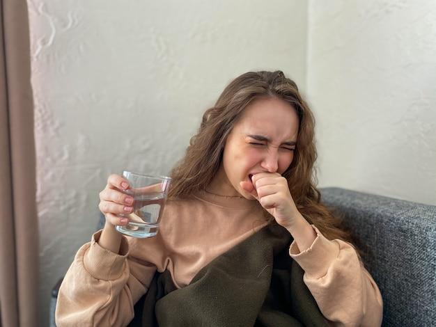 Jonge vrouw blijft thuis geïsoleerd met tekenen van een virale infectie. een vrouw op poliklinische behandeling. huis quarantaine concept, coronavirus