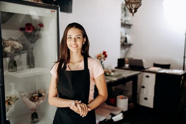 Jonge vrouw bloemist in een zwarte schort staat en glimlacht in een bloemenwinkel.