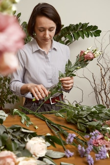 Jonge vrouw bloemist in haar studio een mooi boeket maken