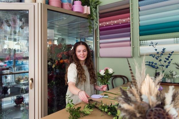 Jonge vrouw bloemist werken met bloemen op de werkplek kleine bedrijfsconcept levensstijl bijgesneden portret bloemen close-up