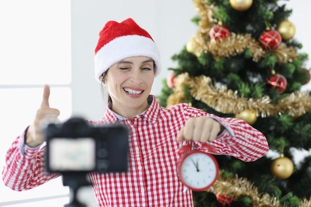 Jonge vrouw blogger in kerstman hoed houdt wekker en knipoogt naar camera nieuwe jaar