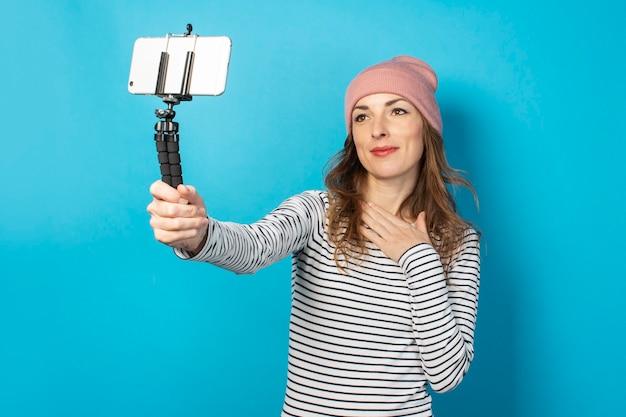 Jonge vrouw blogger maakt foto's van zichzelf aan de telefoon op een blauw oppervlak