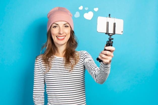 Jonge vrouw blogger maakt foto's van zichzelf aan de telefoon op een blauwe muur. conceptverhaal, vlog, selfie, blog.