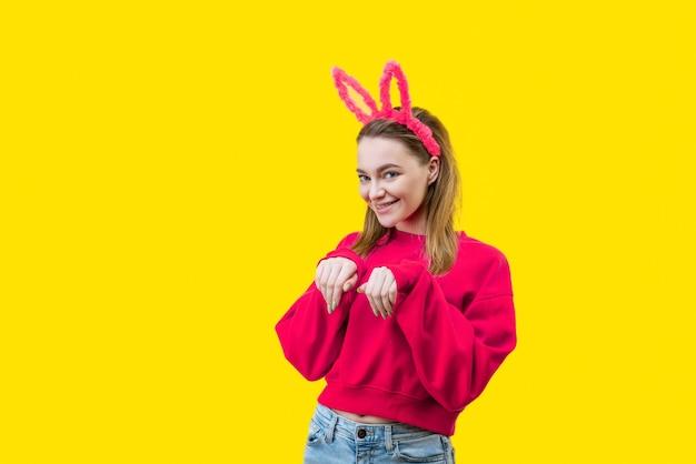Jonge vrouw, blond, met roze konijnenoren en een rode trui op een gele achtergrond