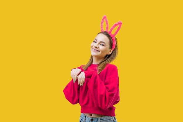 Jonge vrouw, blond, met roze konijnenoren en een rode trui