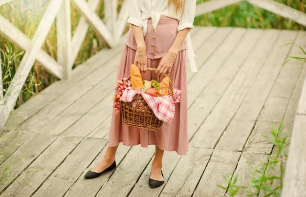 Jonge vrouw blonde met in retro stijl vintage jurk met een picknickmand op een houten pier van het meer