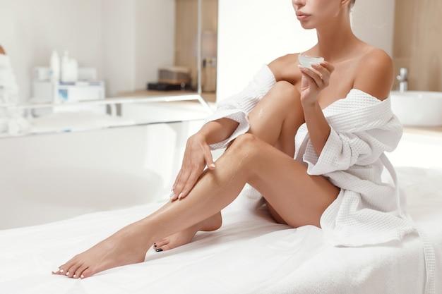 Jonge vrouw bodylotion op benen toe te passen