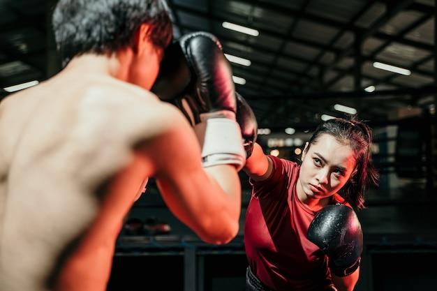 Jonge vrouw bokser doen oefening ponsen concurreren met man tegenstander op bokskamp