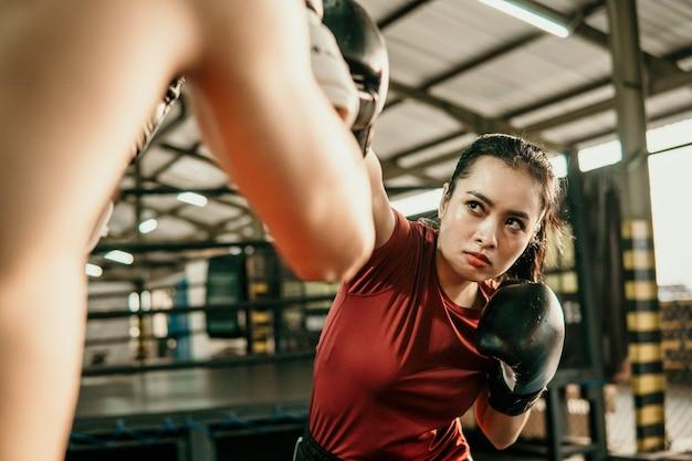 Jonge vrouw bokser oefening raken ponsen concurreren met haar tegenstander op bokskamp