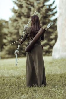 Jonge vrouw boogschutter in groen middeleeuws kostuum staat met haar rug