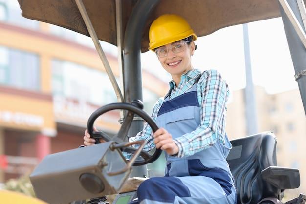 Jonge vrouw bouwer in harde hoed zit achter het stuur van asfalt bestrating