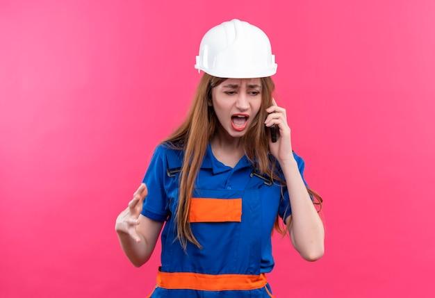 Jonge vrouw bouwer werknemer in bouwuniform en veiligheidshelm schreeuwen met geërgerde uitdrukking tijdens het praten op mobiele telefoon staande over roze muur