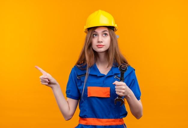 Jonge vrouw bouwer werknemer in de bouw uniform en veiligheidshelm met moersleutel wijzend met wijsvinger naar de zijkant