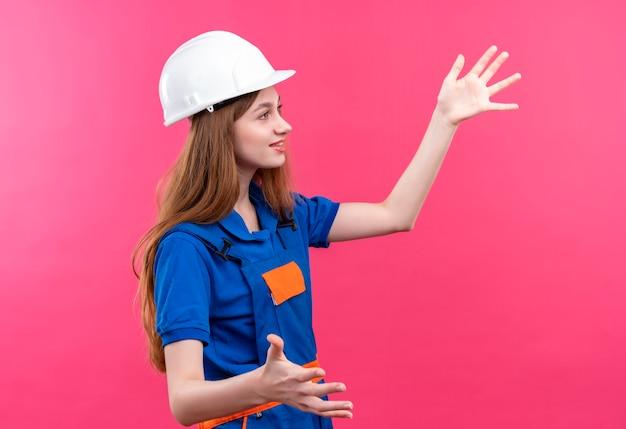 Jonge vrouw bouwer werknemer in de bouw uniform en veiligheidshelm opzij kijken met glimlach op gezicht gebaren met handen permanent over roze muur