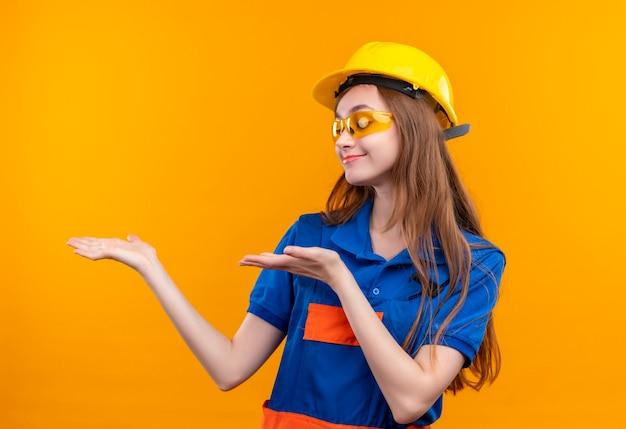 Jonge vrouw bouwer werknemer in de bouw uniform en veiligheidshelm opzij kijken met glimlach op gezicht presenteren met armen van handen staan