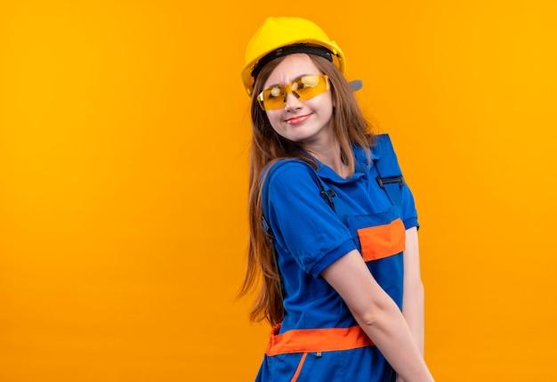 Jonge vrouw bouwer werknemer in de bouw uniform en veiligheidshelm opzij kijken met verlegen glimlach op gezicht staan