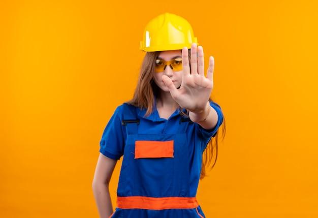 Jonge vrouw bouwer werknemer in de bouw uniform en veiligheidshelm permanent met open hand stopbord maken
