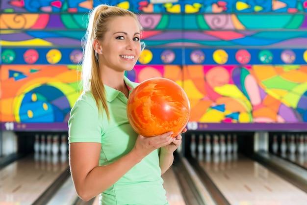 Jonge vrouw bowlen plezier