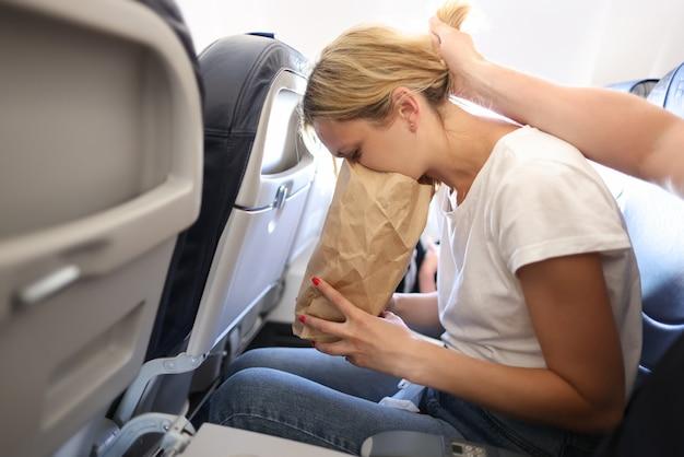 Jonge vrouw braakt in papieren zak in vliegtuigcabine