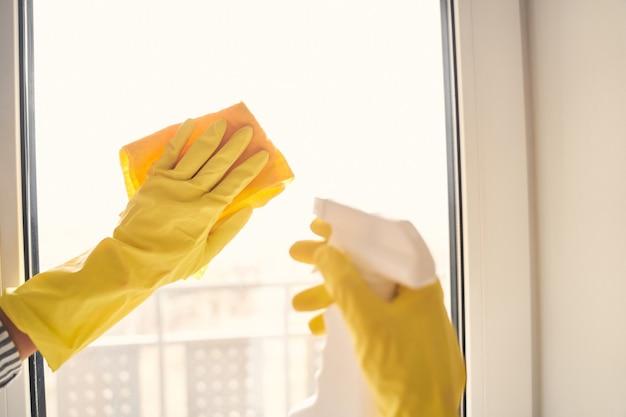 Jonge vrouw brengt haar weekend thuis door terwijl ze ramen schoonmaakt met speciale vloeistof