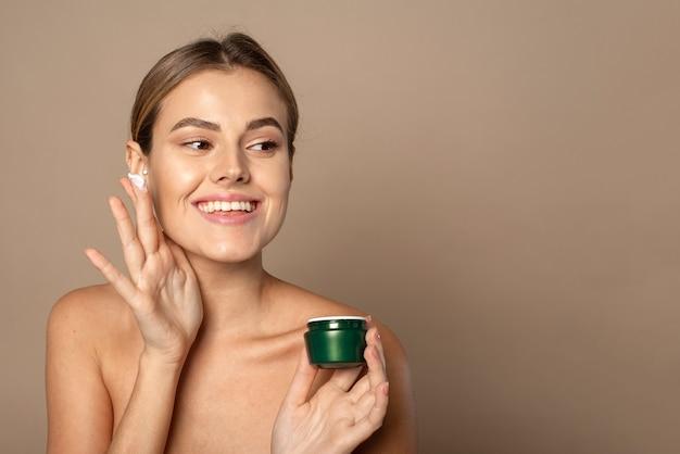 Jonge vrouw brengt vochtinbrengende crème aan op haar gezicht en glimlacht. huidverzorgingsconcept.