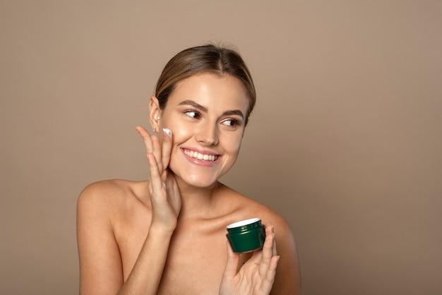 Jonge vrouw brengt vochtinbrengende crème aan op haar gezicht en glimlacht op lichtbruine achtergrond