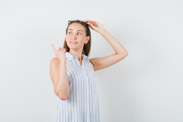 Jonge vrouw bril aan te raken en weg te wijzen in t-shirt vooraanzicht.