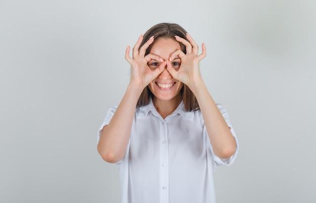 Jonge vrouw bril gebaar in wit t-shirt tonen en op zoek grappig