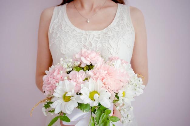 Jonge vrouw, bruid met een boeket bloemen in een witte jurk op een licht roze achtergrond. vrouw met een zilveren ketting om haar nek met een hart hanger.