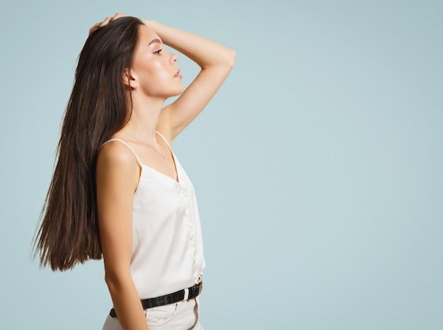 Jonge vrouw brunette op een blauwe achtergrond. zijaanzicht.