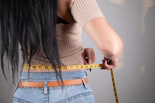 Jonge vrouw buik meten met tape
